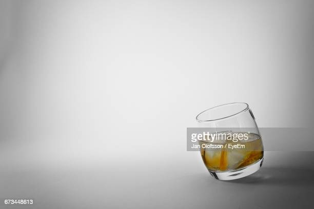 Glass Of Whiskey Against Gray Background