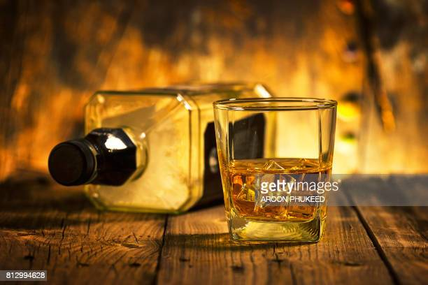a glass of whiskey and empty bottle of whiskey - whisky stock photos and pictures