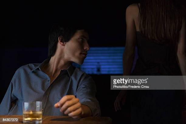 Glass of whiskey on table, man sitting and looking away, rear view of woman standing in the dark