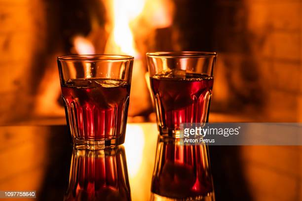Glass of whiskey with ice near the fireplace