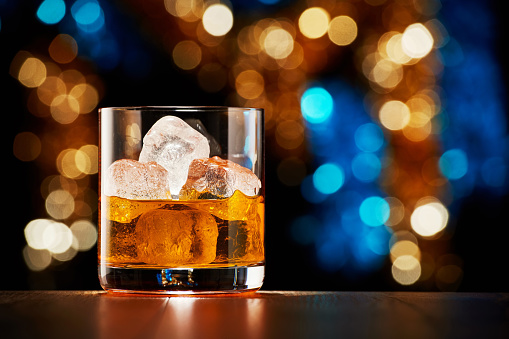 Glass of whiskey with ice on colorful Christmas lights bokeh background 1179303998