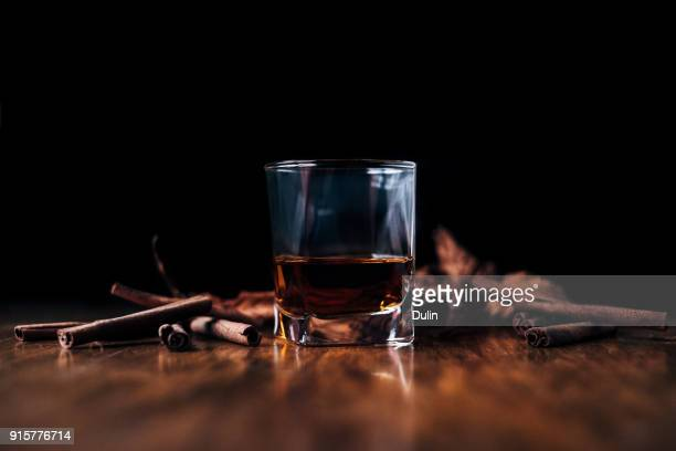 glass of whisky and cinnamon sticks on a table - whiskey stock pictures, royalty-free photos & images