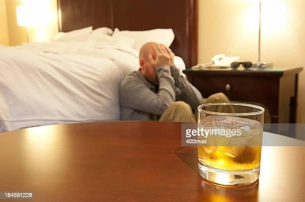 Glass of whisky and distraught man.