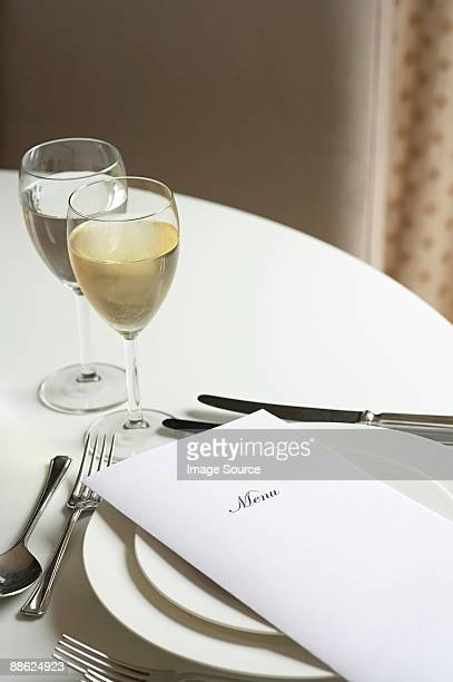 Glass of white wine and a menu on a table