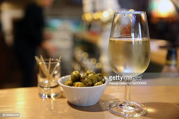 a glass of white wine and olives in a bar - ブラッスリー ストックフォトと画像
