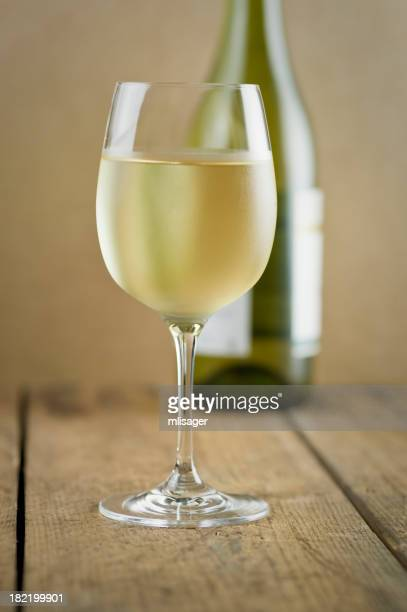 Glass of white wine, bottle and wood table