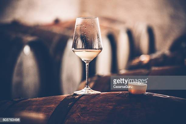 glass of white wine on a barrel in wine cellar - white wine stock pictures, royalty-free photos & images
