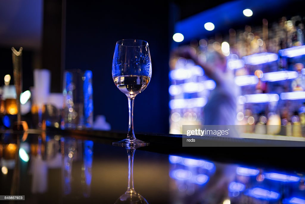 Glass of white wine on bar counter : Stock Photo