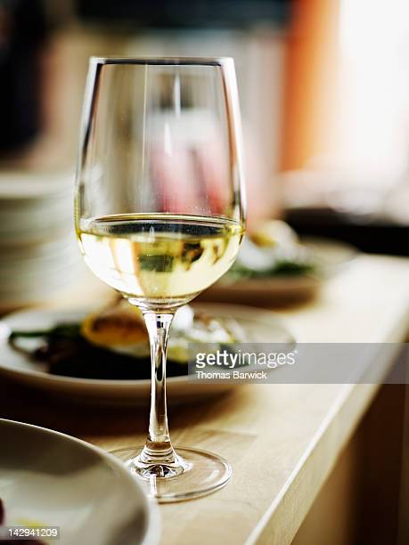 glass of white wine sitting on countertop - white wine stock pictures, royalty-free photos & images