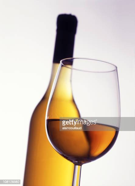 glass of white wine with bottle in background - calvados stock pictures, royalty-free photos & images