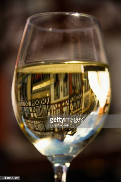 Glass of white wine with reflection of Cochem city center, Germany