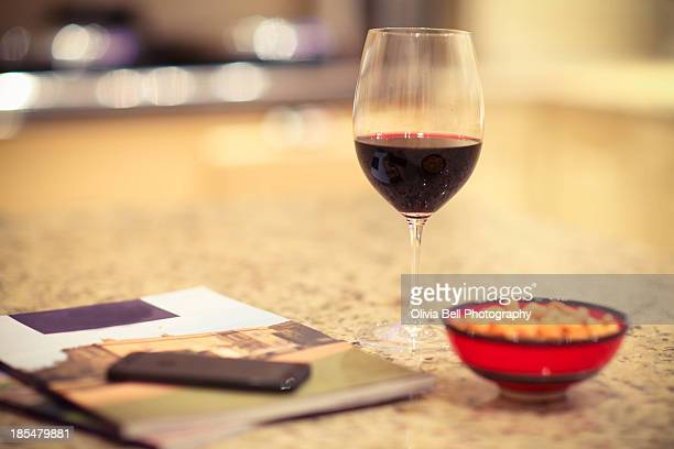 glass of wine, peanuts and magazine - nuts magazine stock photos and pictures