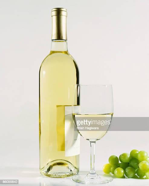 glass of wine with bottle - chardonnay grape - fotografias e filmes do acervo