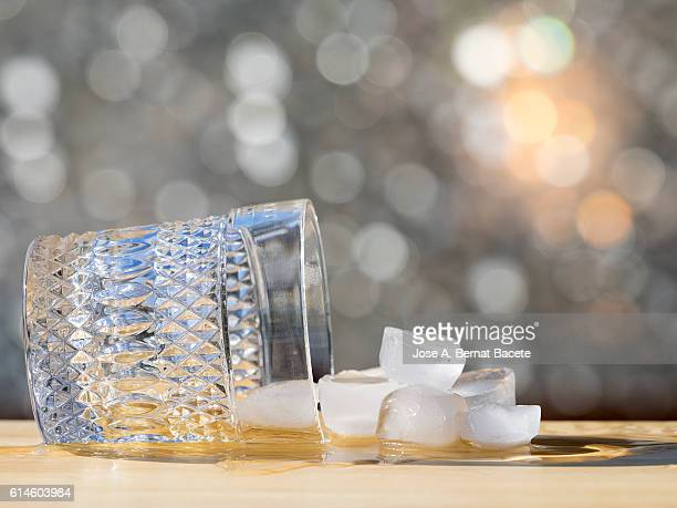 Glass of wisky with fallen ice on a table
