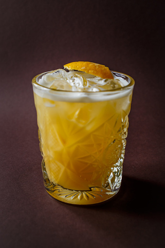 Glass of yellow alcohol cocktail with ice and slice of lemon on elegant dark brown background - gettyimageskorea
