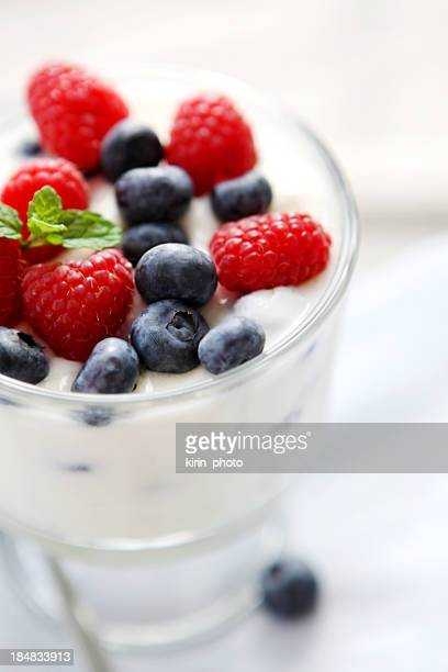 A glass of yogurt with raspberries and blueberries on top
