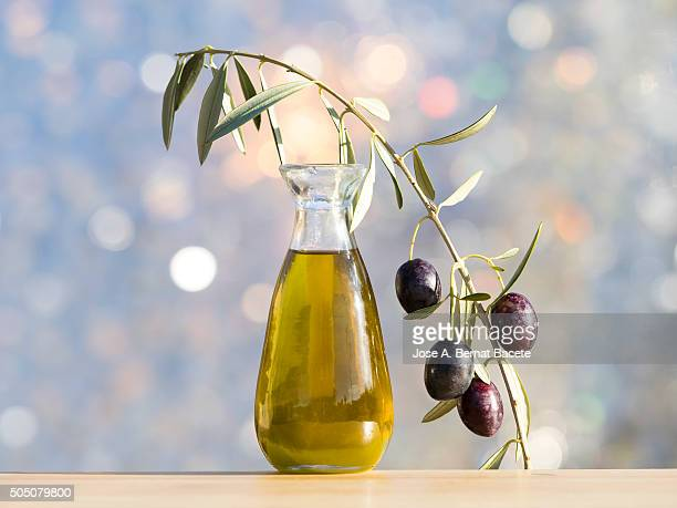 glass oil extra virgin olive oil and a sprig of olive and green olives - cruet stock photos and pictures