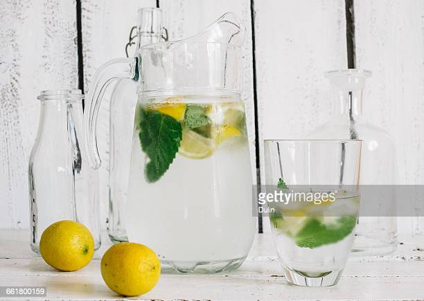 Glass pitcher with fresh lemon, lime, mint and ice-cubes
