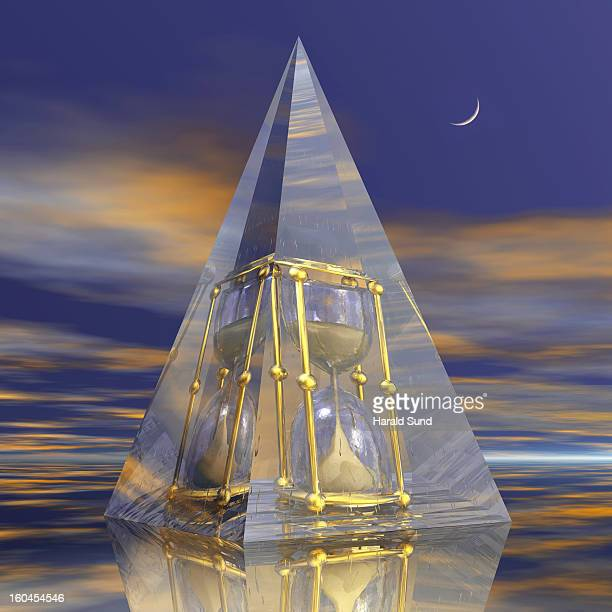 Glass pyramid with encased bronze hour glass