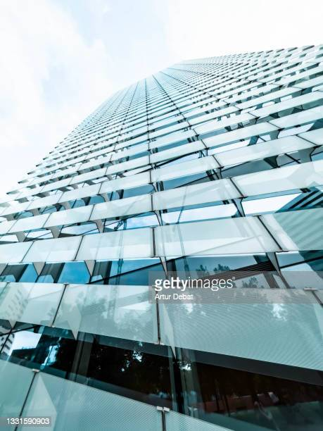 glass skyscraper seen from below with massive vanishing point in barcelona city. - apple computers stock pictures, royalty-free photos & images