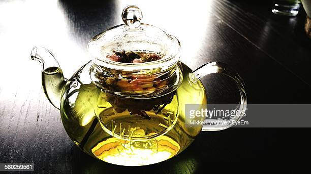 Glass Teapot With Green Tea On Black Table