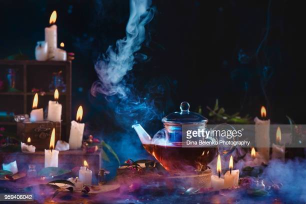 Glass teapot with rising steam in a dark still life with burning candles and smoke. Making herbal tea concept with copy space.