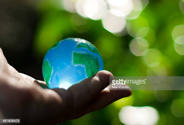 glass toy of earth on the hand - world at your fingertips stock pictures, royalty-free photos & images