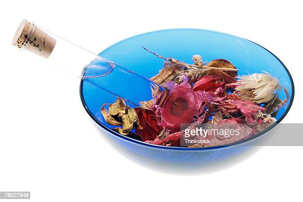 Glass tube in bowl of dried flowers