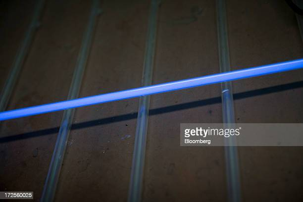 A glass tube part of a neon sign that has been filled with argon gas and a drop of mercury is lit up at Artistic Neon in the Brooklyn borough of New...