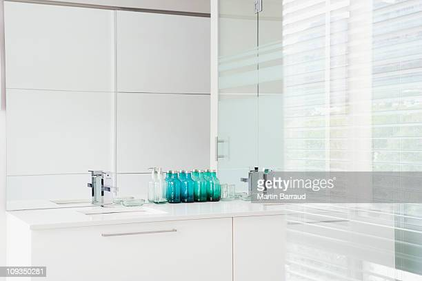 Glass walls and sink in modern, white bathroom