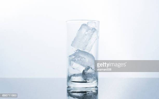 glass water with ice water in glass on wet plate and white background  drink and party concept
