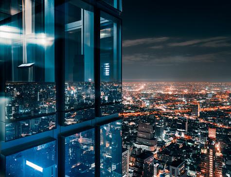 Glass window with glowing crowded city 1127251935