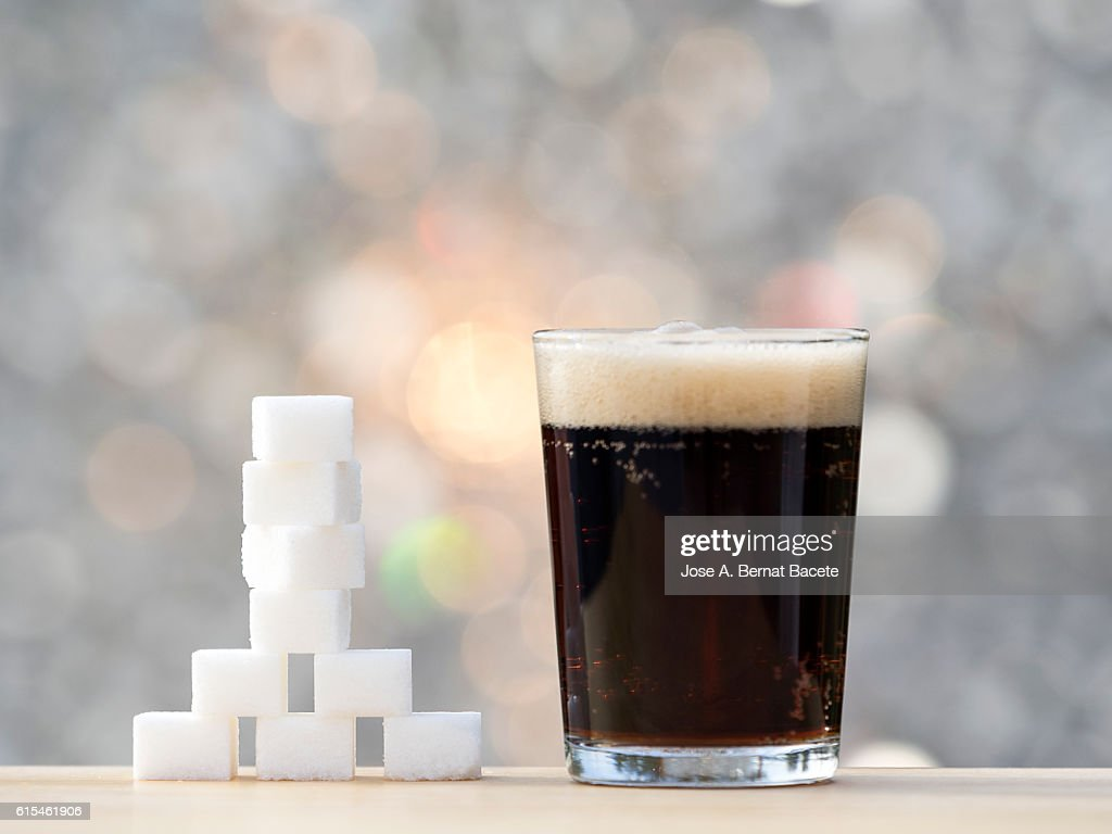 Glass with cola and its equivalent in sugar cubes : Stock Photo
