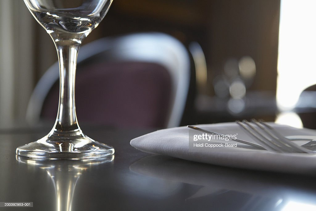 Glass with fork and knife on napkin on table : Stock Photo