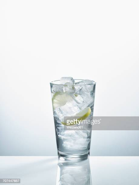 Glass with mineral water, ice cubes and slices of lemon in front of white background