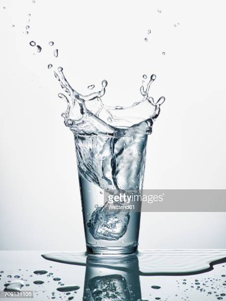 Glass with sinking ice cube and splashing water in front of white background