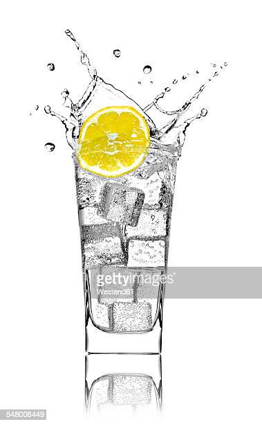 Glass with soda water, ice cubes and slice of lemon in front of white background