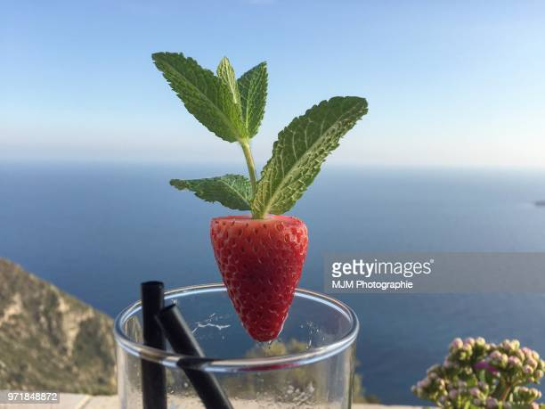 Glass with strawberry garnish overlooking the Mediterranean Sea