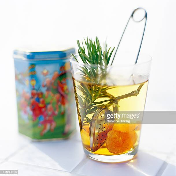 A glass with tea rosemary and dried fruit.