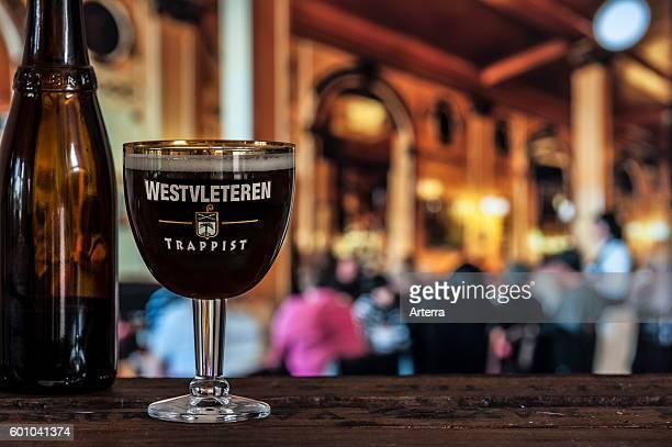 Glass with trappist Westvleteren best beer in the world brewed in the SintSixtusabdij / Abbey of Saint Sixtus served in busy cafe in Belgium