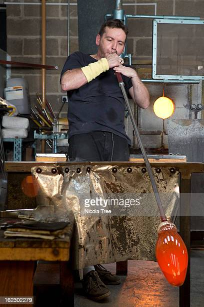 Glassblower blowing a large piece of molten glass