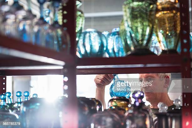 Glassblower inspecting finished glassware