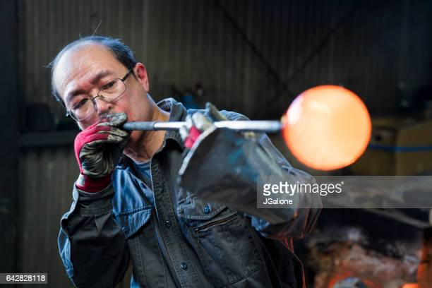 glassblower shaping molten glass - jgalione stock pictures, royalty-free photos & images