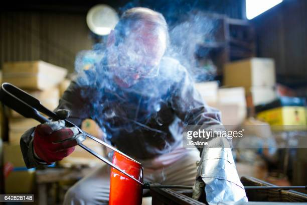 Glassblower using specialist tools to shape a molten glass bowl