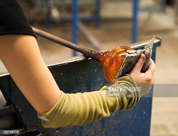 Glassblower using wet newspaper to shape the glass