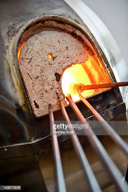 Glassblowers heating glass in kiln