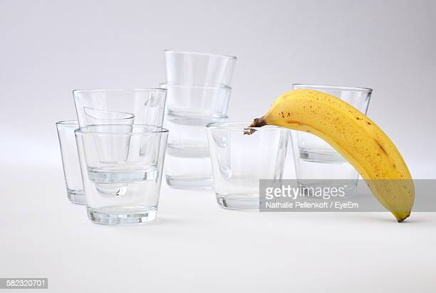 glasses and banana against white background - nathalie pellenkoft stock pictures, royalty-free photos & images