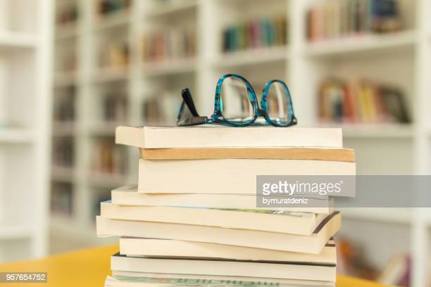 glasses and book at library - reading glasses stock pictures, royalty-free photos & images