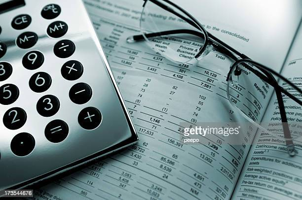 Glasses and calculator laying on financial records.