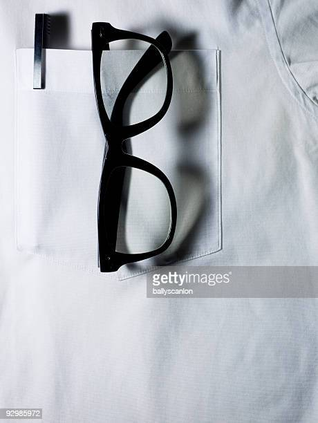 Glasses and pen in white shirt pocket.